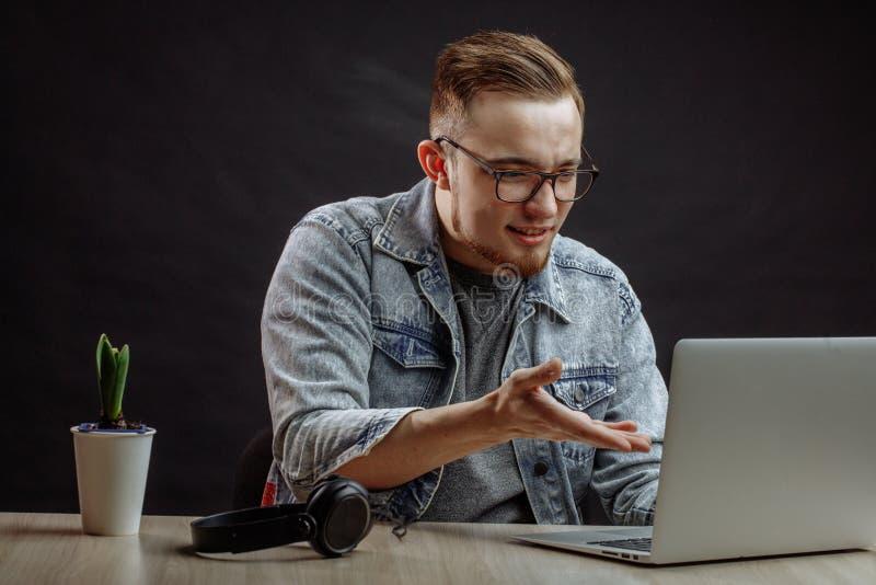 Netter Mann des Ingwers, der zum Schirm des Laptops darstellt lizenzfreie stockfotos
