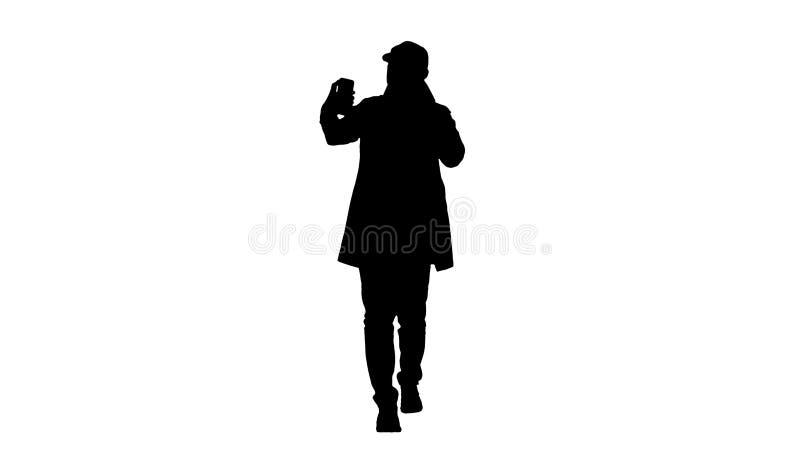 Netter Mann des Schattenbildes im Mantel, der das Foto macht selfie macht lizenzfreie abbildung