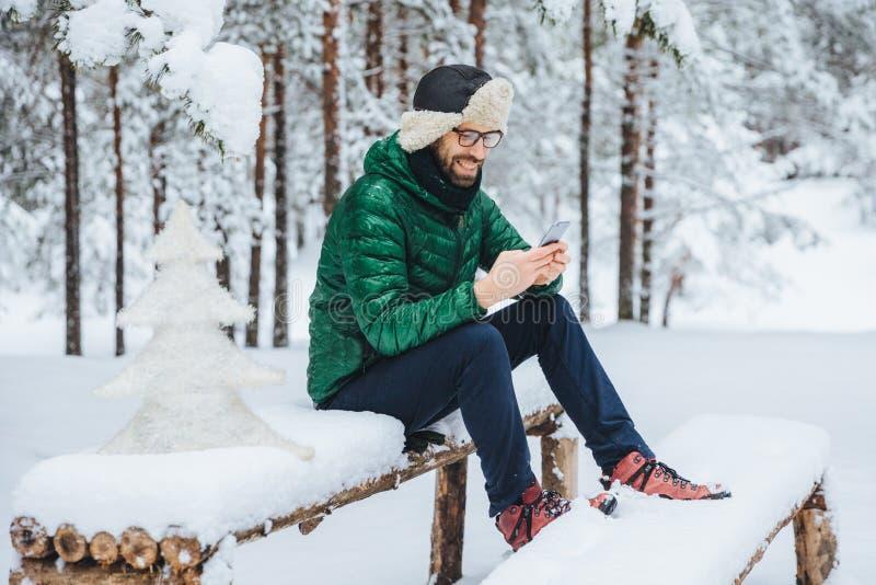 Netter Mann genießt Kommunikation am intelligenten Telefon und Einsamkeit, ruhige Atmosphäre, sitzt auf der Holzbank, die mit Sch stockbilder
