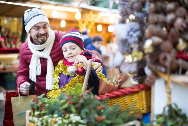 Netter Mann mit kleiner Tochter nahe Weihnachtsdekoration lizenzfreie stockfotos