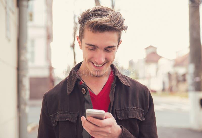 Netter Mann unter Verwendung des Mobiltelefons draußen stockfotografie