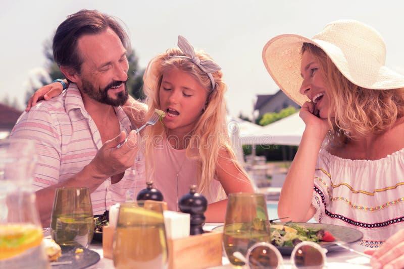 Netter mitfühlender Vati, der seine Tochter mit Salat einzieht lizenzfreie stockbilder
