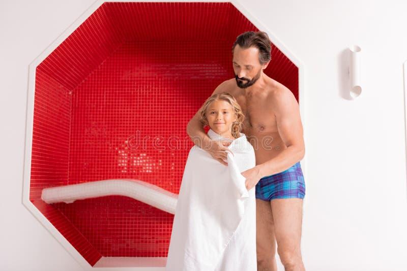 Netter mitfühlender Vati, der Tuch um seine Tochter einwickelt lizenzfreies stockfoto