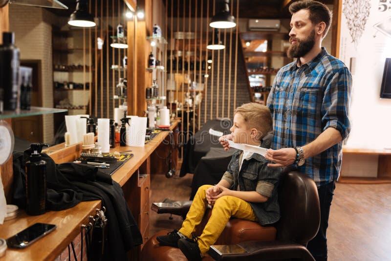 Netter netter Junge, der einen Friseursalon besichtigt lizenzfreies stockfoto