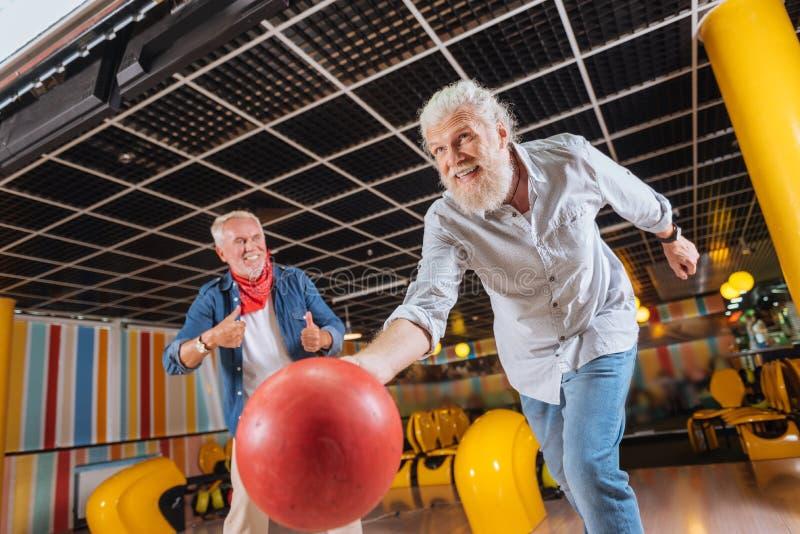 Netter positiver Mann, der im Bowlingspiel am Tag lächelt stockfoto
