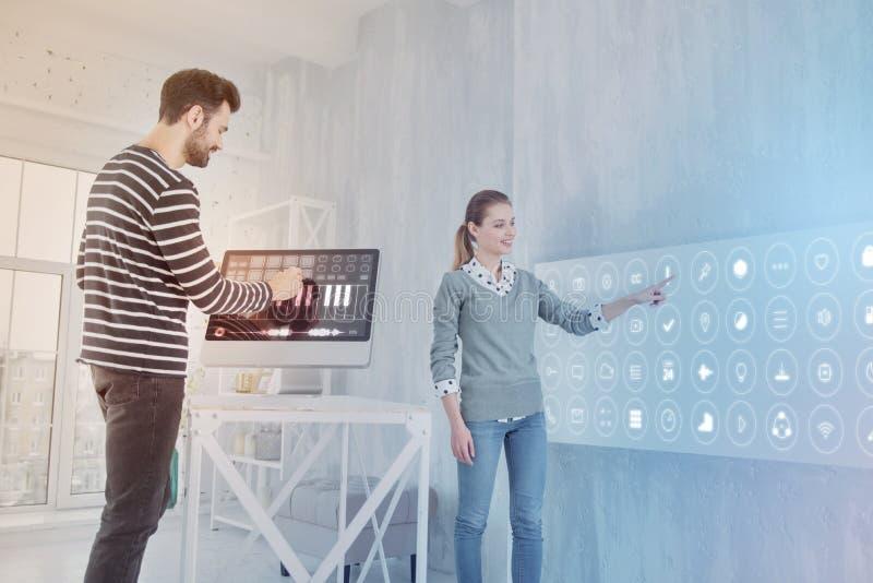 Netter Programmierer, der an Computer während sein Mitarbeiter nahe steht arbeitet stockbilder