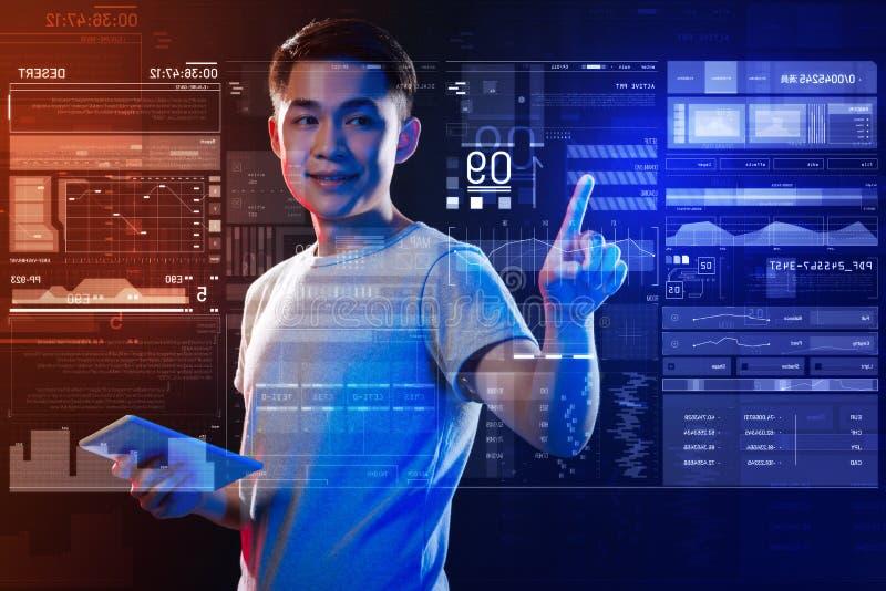 Netter Programmierer, der mit einer Tablette und einem Arbeiten steht lizenzfreie stockfotografie