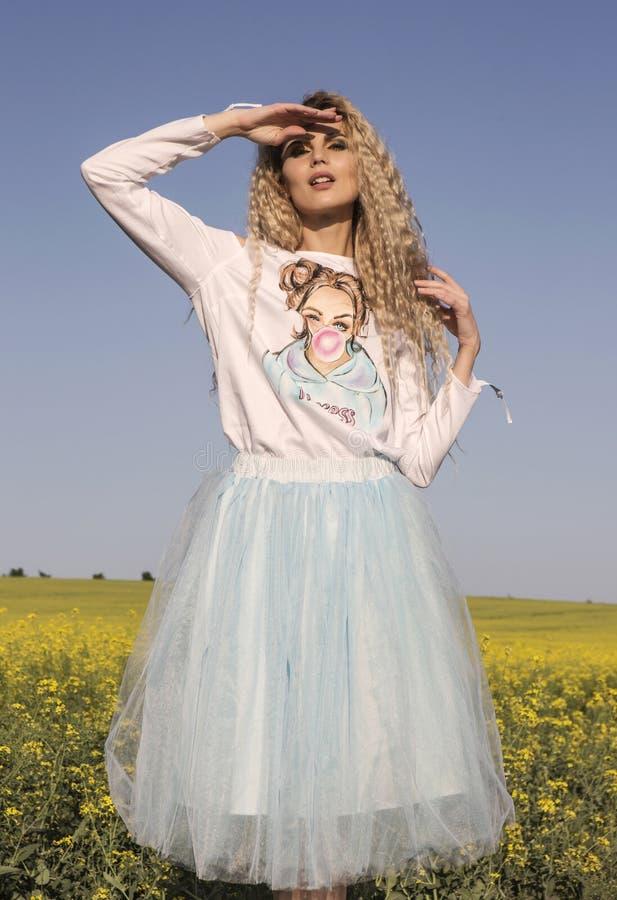 Netter Puppenblick Weißes und blaues romantisches Kleid über blauem Himmel stockbild
