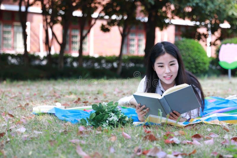 Netter reizender asiatischer chinesischer hübscher Mädchenabnutzungs-Studentenanzug in der Schule, die auf Grasrasen-Lesebuch lie lizenzfreie stockfotos