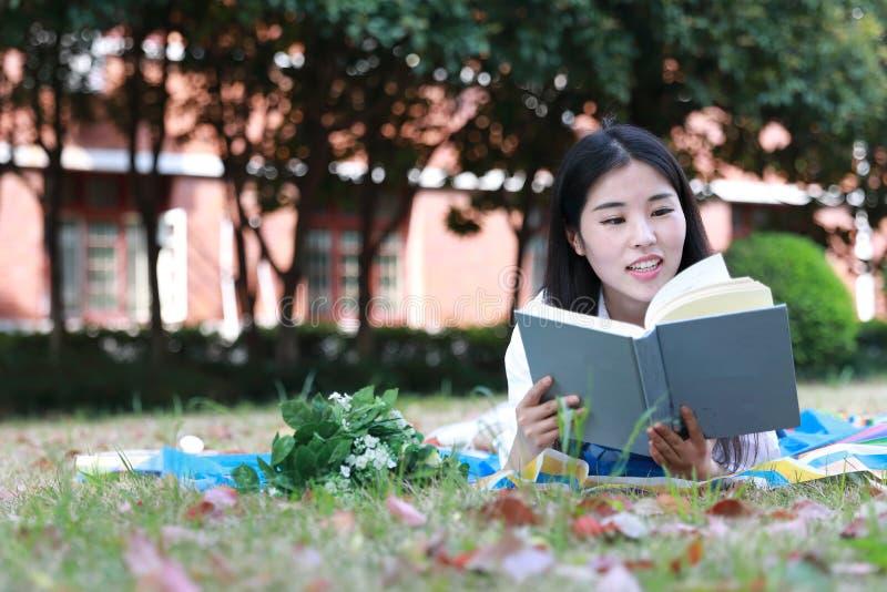 Netter reizender asiatischer chinesischer hübscher Mädchenabnutzungs-Studentenanzug in der Schule, die auf Grasrasen-Lesebuch lie stockbild