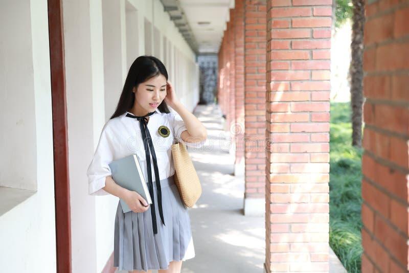 Netter reizender asiatischer chinesischer hübscher Mädchenabnutzungs-Studentenanzug in der Schule in der Klasse genießen Freizeit lizenzfreie stockfotografie