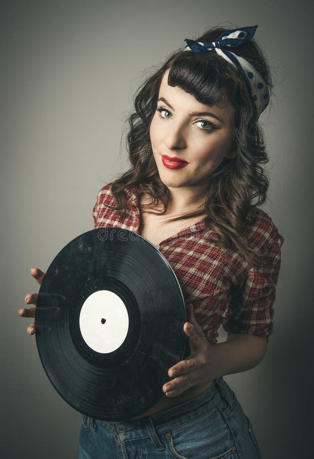 Netter Retro- Stift herauf das Mädchen, das eine Vinylaufzeichnung hält lizenzfreies stockfoto