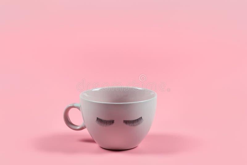 Netter rosa Kaffee- oder Teebecher mit falschen Peitschen auf einem rosa Hintergrund mit Kopienraum lizenzfreie stockfotos