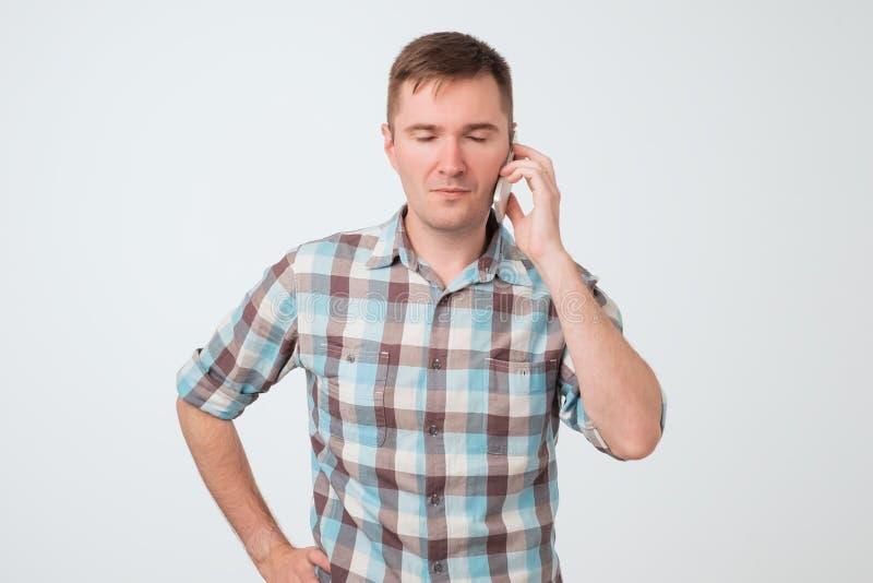 Netter ruhiger junger Mann, der versucht, den Patienten zu bleiben spricht am Telefon über weißem Hintergrund lizenzfreies stockbild