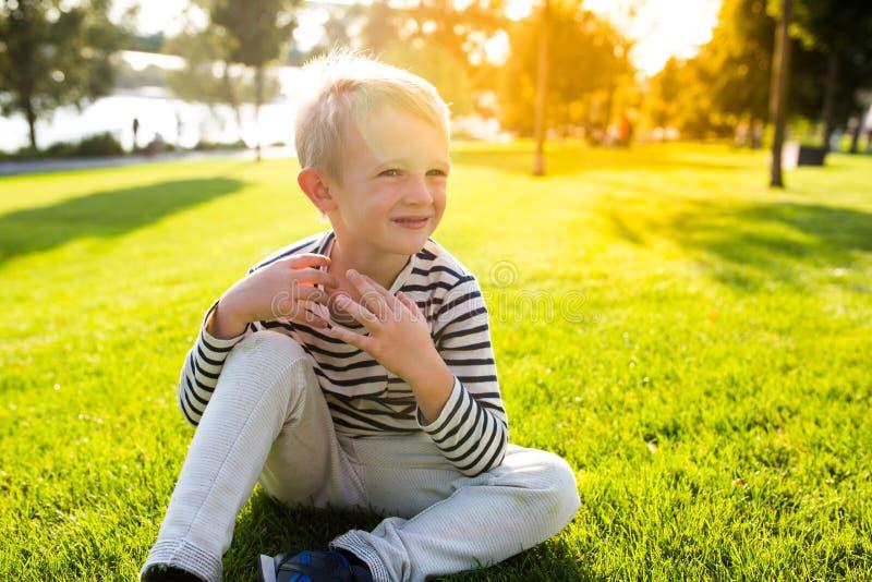 Netter schöner glücklicher kleiner Junge sitzen auf dem Gras, das Sommerzeit genießt lizenzfreies stockbild