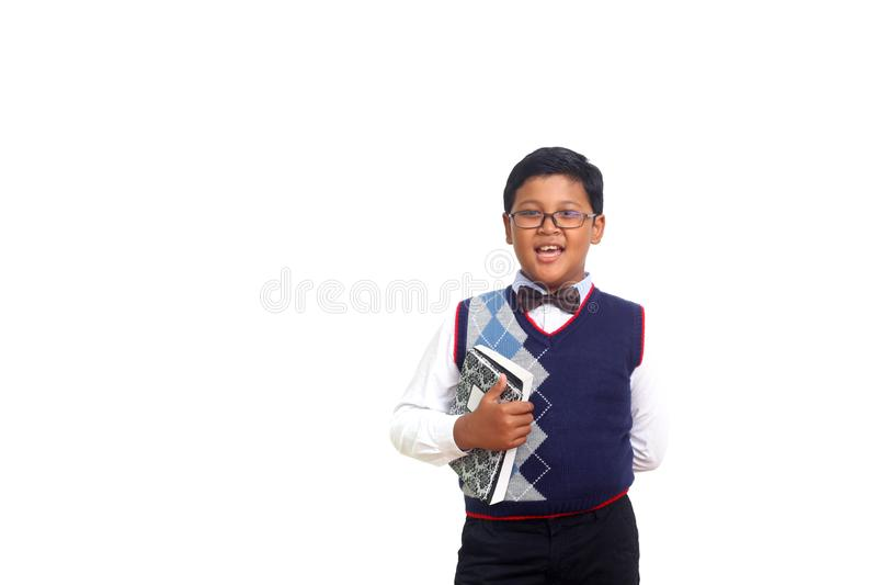 Netter Schüler, der auf Kamera beim Tragen von Gläsern und Halten eines Buches, lokalisiert auf weißem Hintergrund lächelt stockfotografie