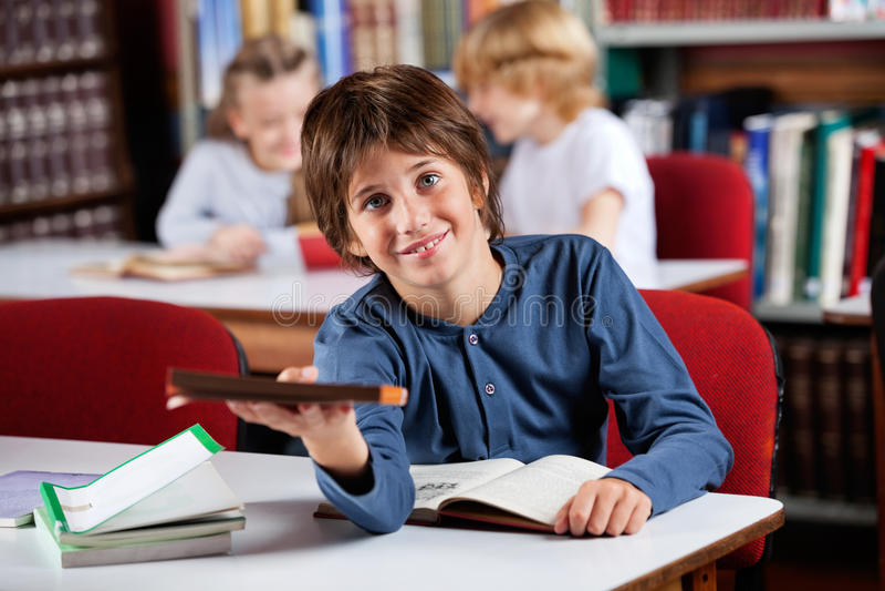 Netter Schüler, der Buch beim bei Tisch sitzen gibt stockbilder