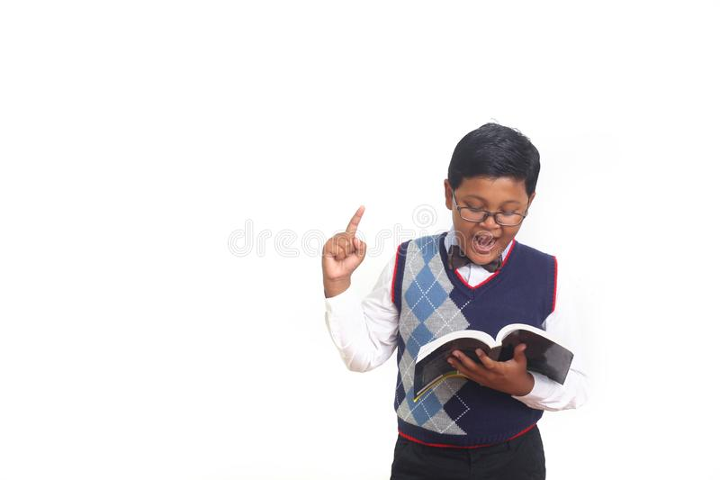 Netter Schüler, der eine Idee beim Tragen von Gläsern und Halten eines Buches, lokalisiert auf weißem Hintergrund erhält stockfotos