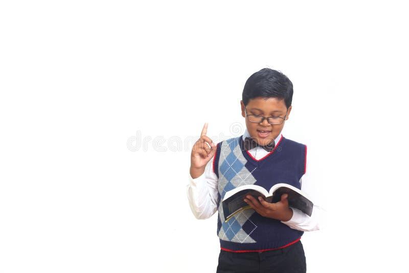 Netter Schüler, der eine Idee beim Tragen von Gläsern und Halten eines Buches, lokalisiert auf weißem Hintergrund erhält stockbild