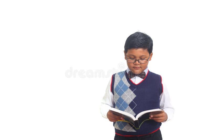 Netter Schüler, der ernsthaft ein Buch beim Tragen von den Gläsern, lokalisiert auf weißem Hintergrund liest stockbild