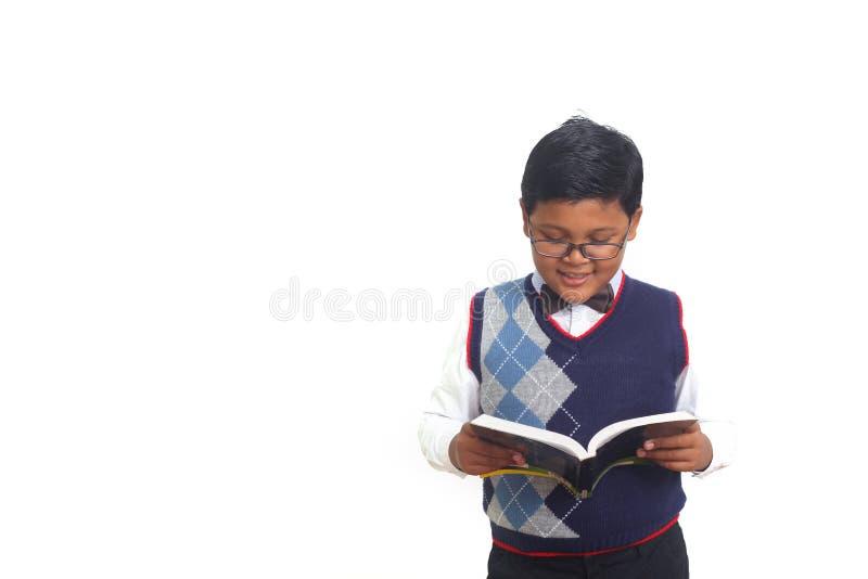 Netter Schüler, der ernsthaft ein Buch beim Tragen von den Gläsern, lokalisiert auf weißem Hintergrund liest stockfoto