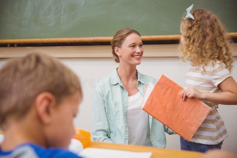 Netter Schüler, der ihren Lehrer während der Klassendarstellung schaut stockfotografie