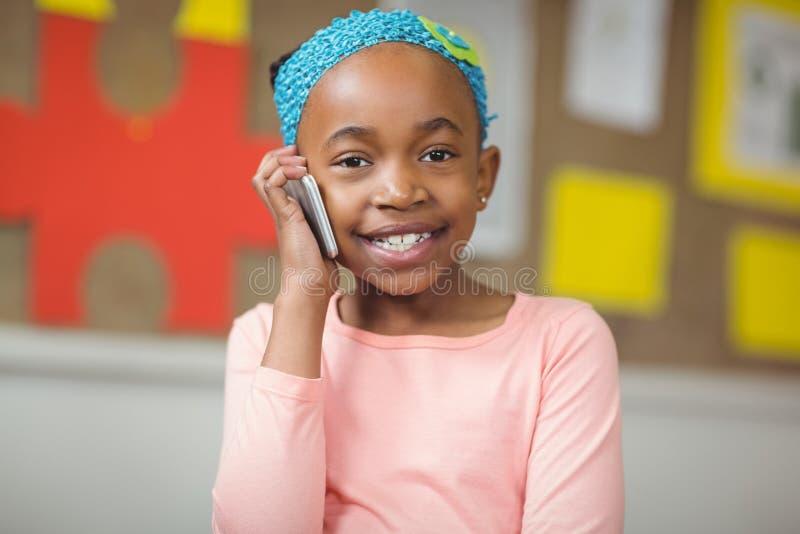 Netter Schüler, der mit Smartphone in einem Klassenzimmer anruft lizenzfreie stockfotos