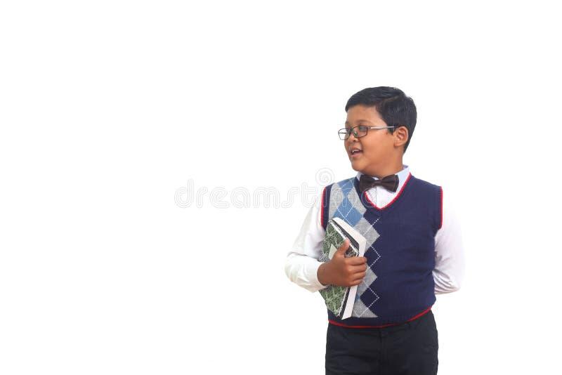 Netter Schüler, der neben ihm beim Tragen von Gläsern und Halten eines Buches, lokalisiert auf weißem Hintergrund lächelt und sch stockfotografie