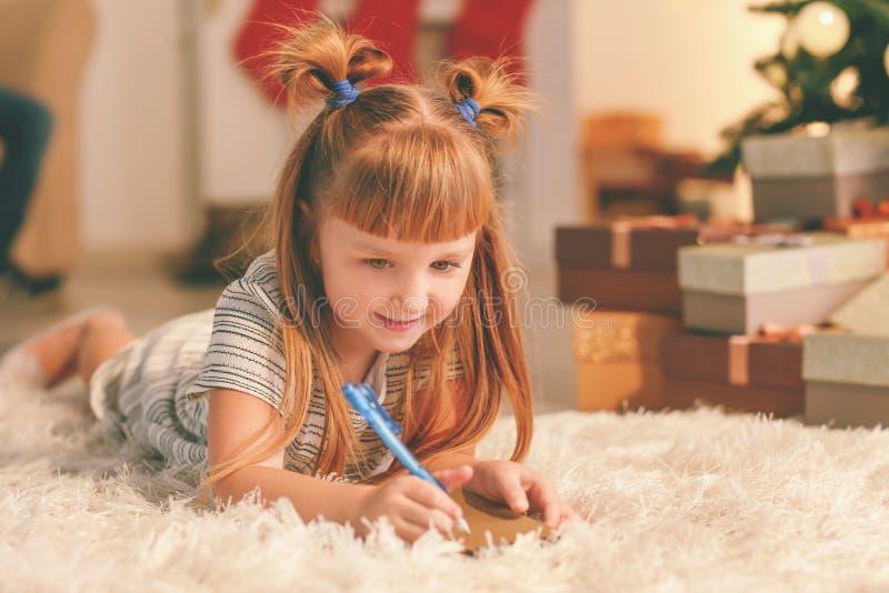 Netter Schreibensbuchstabe des kleinen Mädchens zu Santa Claus zu Hause stockbild