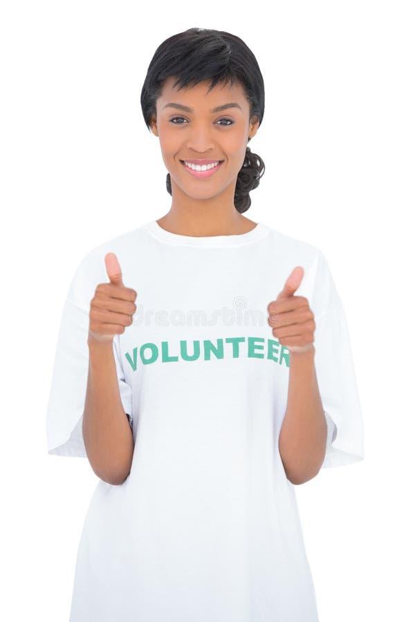 Netter schwarzer behaarter Freiwilliger, der Daumen aufgibt stockfotografie