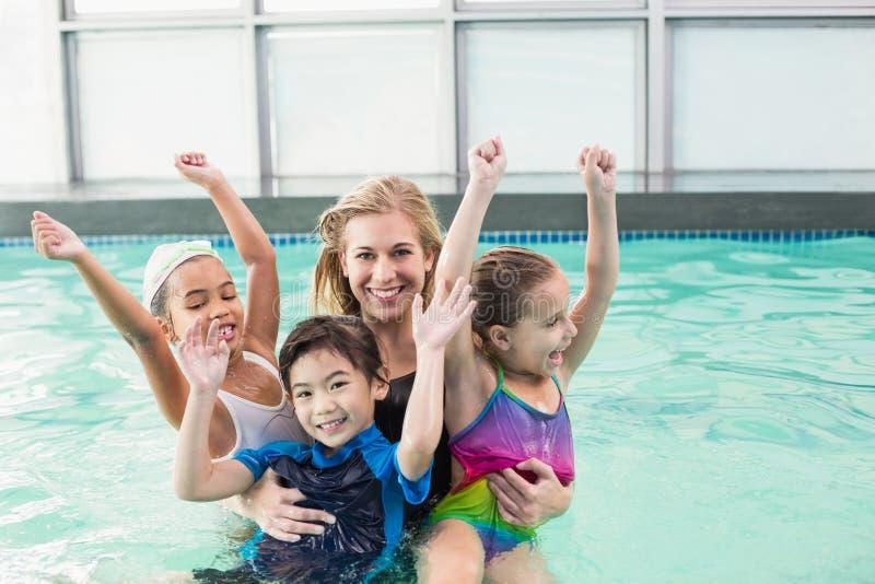 Netter Schwimmkurs im Pool mit Trainer lizenzfreie stockbilder