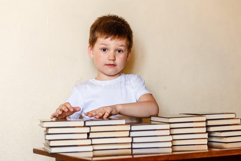 Netter sechsjähriger Junge, der an einem Schreibtisch mit Stapeln Büchern sitzt lizenzfreie stockbilder