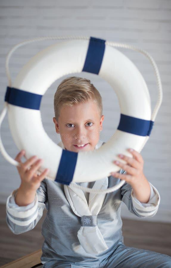 Netter Seemannjunge, der eine Schwimmweste hält lizenzfreie stockfotografie