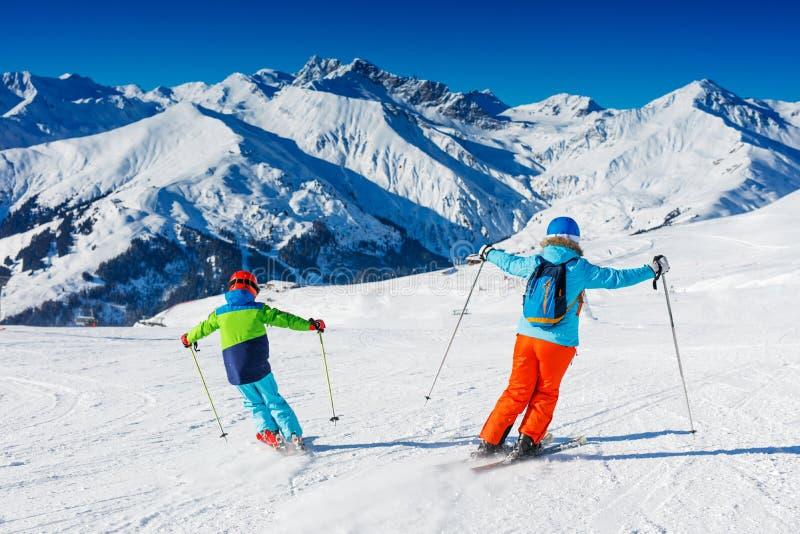 Netter Skifahrerjunge mit seiner Mutter, die Spaß in einem Winterskiort hat stockfoto