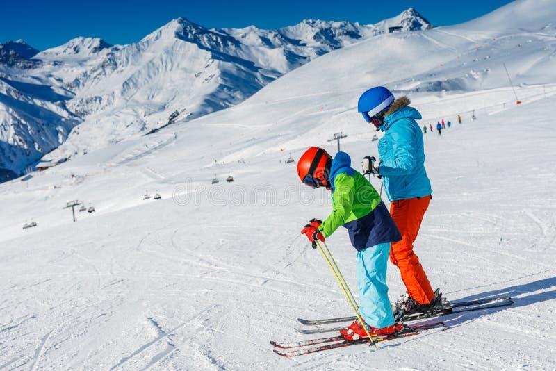 Netter Skifahrerjunge mit seiner Mutter, die Spaß in einem Winterskiort hat stockbilder