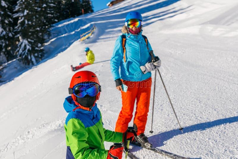 Netter Skifahrerjunge mit seiner Mutter in einem Winterskiort lizenzfreies stockbild