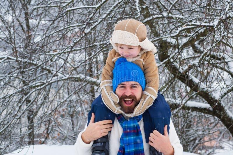Netter Sohn umarmt seinen Vati auf Winterurlaub Der Vater, der Sohn-Fahrt unterst?tzen gibt ein, im Park Vati- und Babysohn, der  lizenzfreie stockfotografie