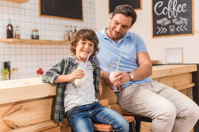 netter Sohn und seine trinkenden Milchshaken des Vaters stockbilder