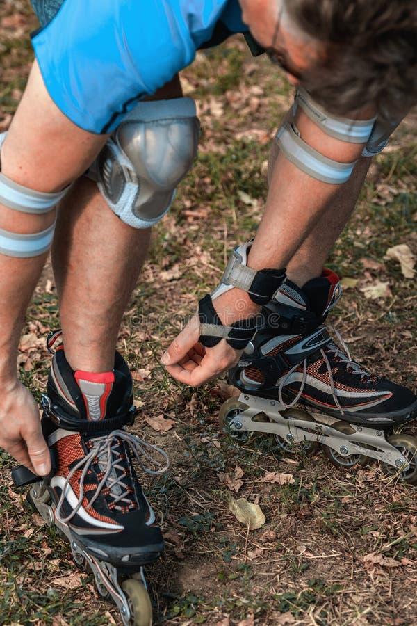 Netter sportlicher Mann 50-55 Jahre alt, die Rollschuhlaufen im Park in der Herbstsaison reiten, rollerblading als gesunde Übung  lizenzfreies stockfoto