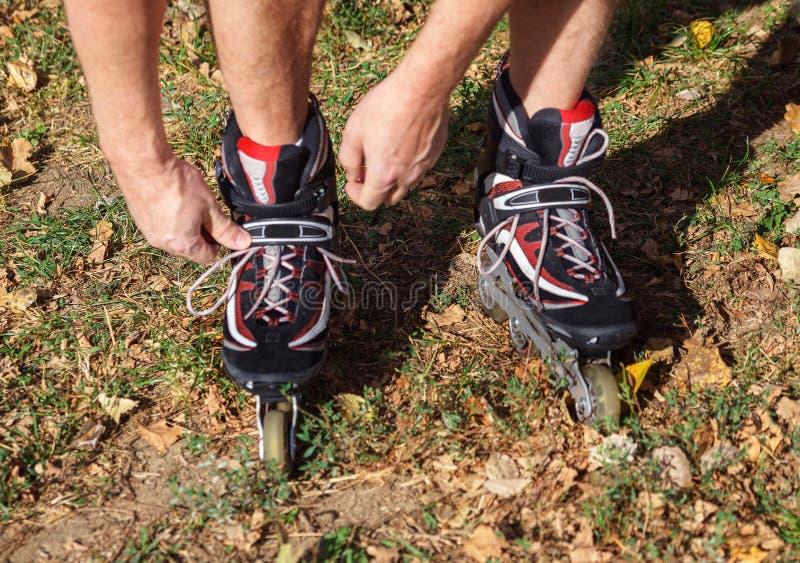 Netter sportlicher Mann 50-55 Jahre alt, die Rollschuhlaufen im Park in der Herbstsaison reiten, rollerblading als gesunde Übung  stockfotografie
