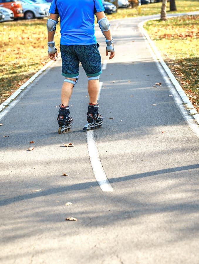 Netter sportlicher Mann 50-55 Jahre alt, die Rollschuhlaufen im Park in der Herbstsaison reiten, rollerblading als gesunde Übung  lizenzfreie stockfotos