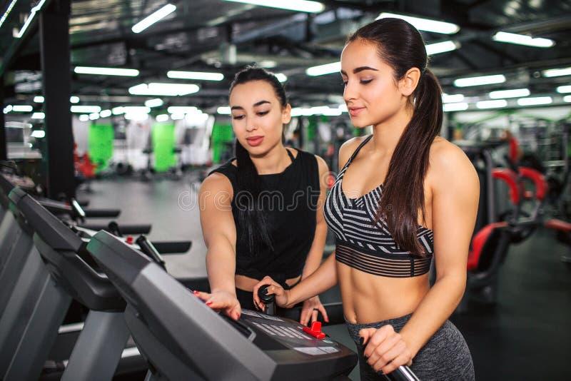 Netter Stand der jungen Frau auf Laufbahn und Blick auf seine Platte Asiatische weibliche Trainerhilfe sie, Maschineneinstellunge lizenzfreie stockfotos
