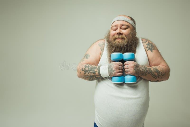 Netter starker Mann, der das Lieben hopfenreich mit Sportgewichten tut stockfotografie