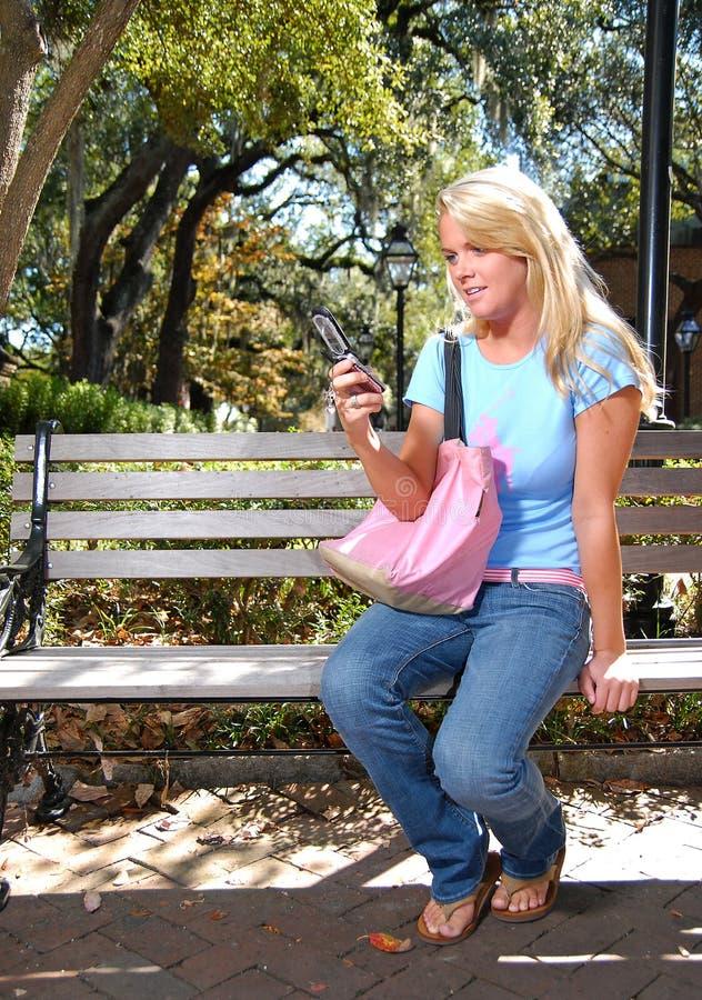Netter Student auf Handy stockfotografie