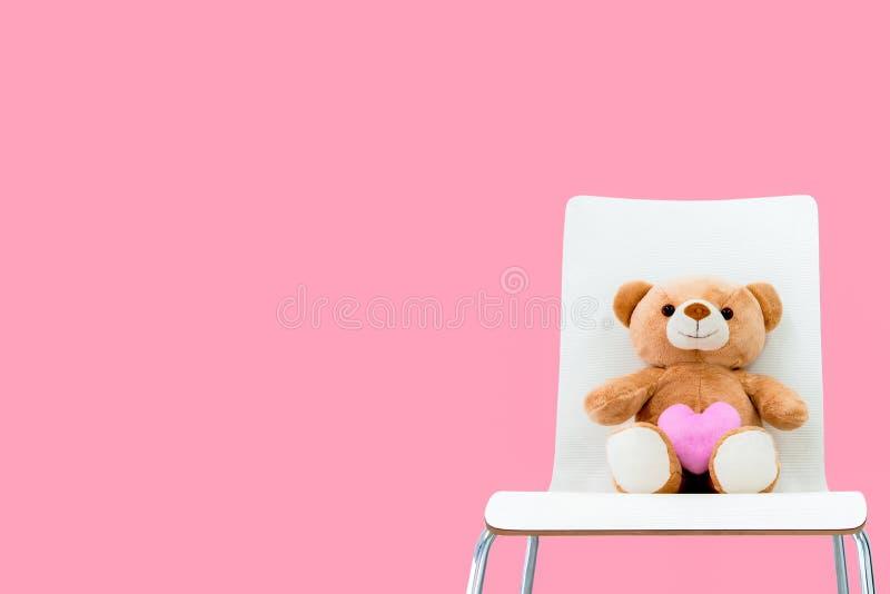 Netter Teddy Bear mit rosa Herzform sitzen auf einem Stuhl in einem rosa Raum lizenzfreie stockbilder