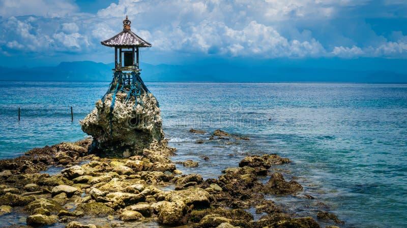 Netter Tempel auf dem Ufer durch das Meer auf Nusa Penida mit drastischen Wolken über Bali, Indonesien lizenzfreies stockfoto