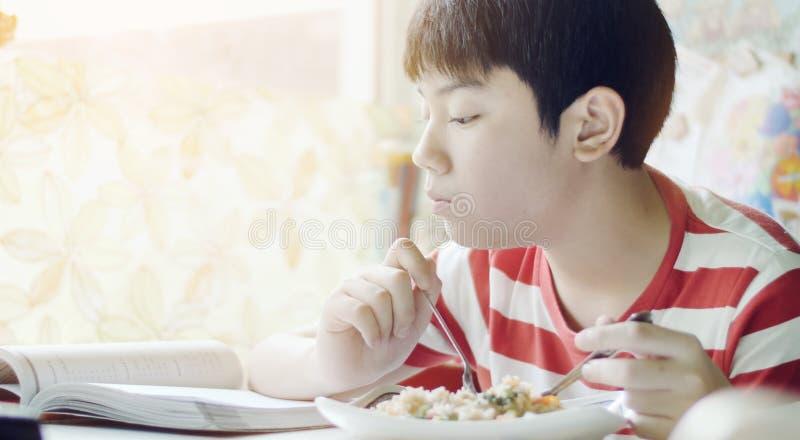 Netter thail?ndischer Junge, der Nahrung des gebratenen Reises auf der wei?en Tabelle im Wohnzimmer isst stockfotografie