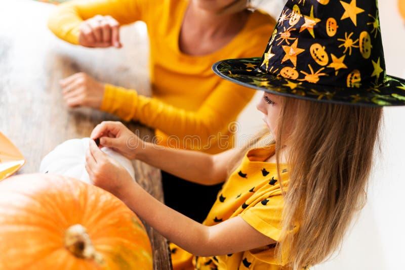 Netter tragender Hexenhut des kleinen Mädchens, der hinter einer Tabelle mit ihrer Mutter, weiße Halloween-Kürbise verzierend sit lizenzfreie stockbilder