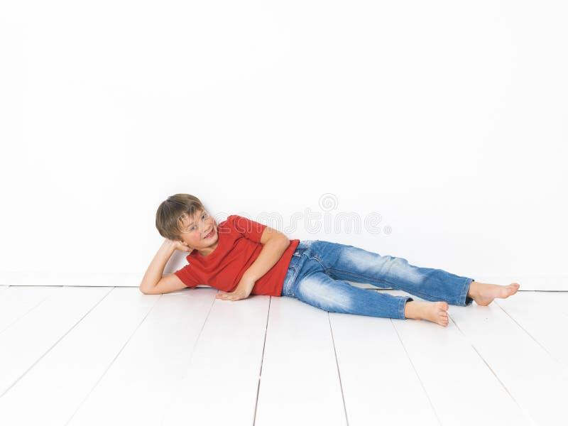 Netter und blonder Junge mit rotem Hemd und Blue Jeans wirft auf weißem Bretterboden auf lizenzfreie stockfotografie