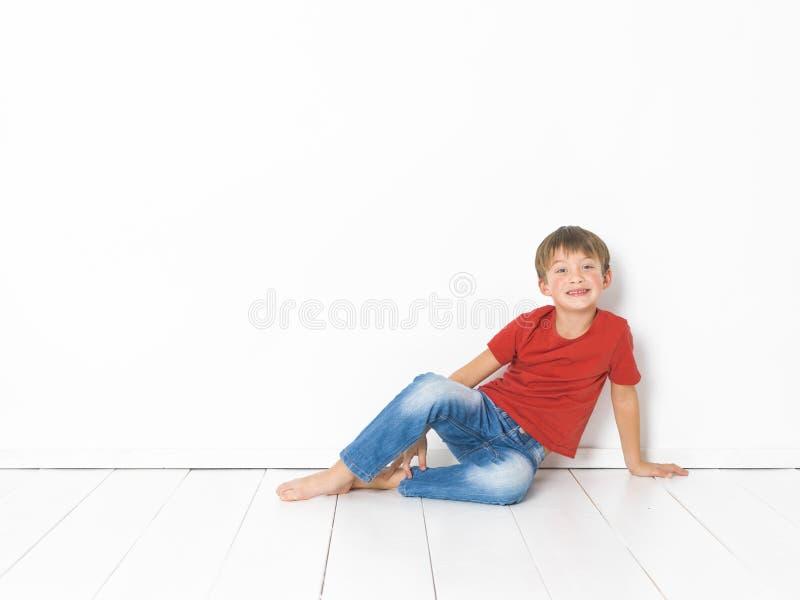Netter und blonder Junge mit rotem Hemd und Blue Jeans wirft auf weißem Bretterboden auf stockfotografie